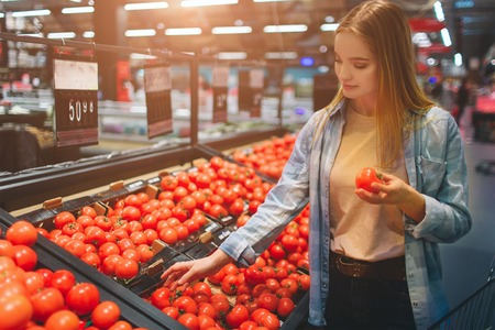 Beautiful and awesome lady is at grossary store and choosing some tomatoes to buy. She has chosen one tomato and hold it in her hand. Close up. Stock Photo