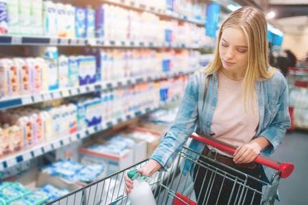 Un'immagine in cui una ragazza di bell'aspetto e attraente mette una bottiglia di latte nel suo cestino grossolano. Lo sta facendo molto attentamente. Taglia vista. Archivio Fotografico - 97593526