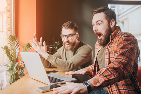 Very emotional picture of guys looking to the laptops screen. One of them is very amazed and opened his mouth very wide while another is just looking to the screen. Stock Photo