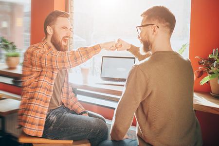 幸せで感情的な男性が一緒に座って叫んでいます。彼らは拳を組み立てた。その絵はポジティブに感情的だ。閉じて