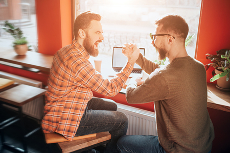 Nice and good picture of two guys sitting at the table in front of the big window and holding each other with that fists. THey are congratulating each other 写真素材