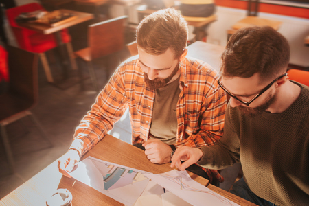Close up of two adult and bearded guys sitting at the table and studying graphics in documents. They are preparing for demonstation this materials.