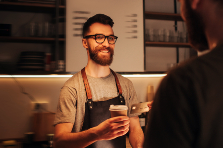 A picture of bearded hipster barmen that wears glasses standing behind the bar stand and holding a cup of coffee that he did for the customer. The barman looks happy and smiling.