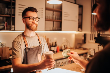 A picture of bearded barmen that wears glasses standing behind the bar stand and holding a cup of coffee that he did for the customer. The barman looks serious. Seems like he doesnt have a mood.