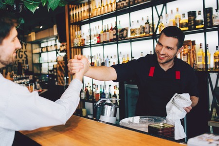 Cut view of barman greeting his friend and shaking his hand. He is happy to see his friend. Everything is situated in a nightclub.