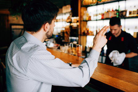 A picture of customer sitting towards the barman. He wants to order some cocktails and showing it with his right hand. THe barman doesnt see it.