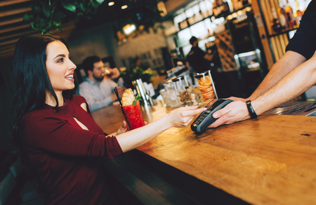 A picture of stunning girl sitting close to barman and paying for her order. She gives a credit card to barman to pay for that. Zdjęcie Seryjne