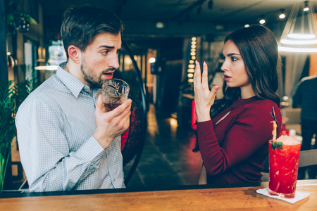 Angry young woman shows her hand with the ring on it to the man. He looks amazed. His face is full of different emotions.