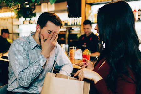 Sad picture of man covering hie face with the hand. He doesnt understand what his girlfriend is talking about. But she looks happy. Reklamní fotografie