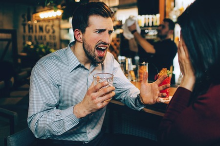 A picture of guy screaming to the girl. He is tired and angry at the same time. She is stressed as well. Reklamní fotografie