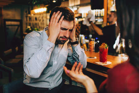 Handsome guy is covering up his ears. He cant listen to her voice anymore. He is tired of that. Reklamní fotografie