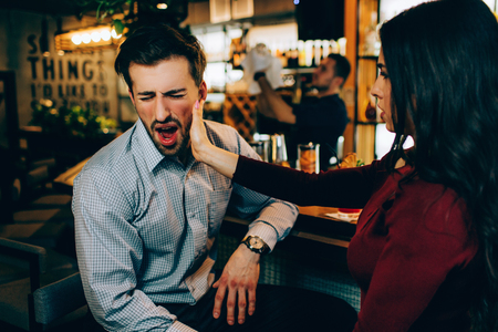 Girl is beating the chick of her partner in the night club. It is painful. He feels that. Guy has closed his eyes. He wasnt prepared for that.
