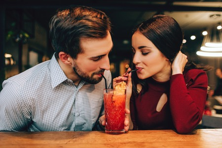 Nice picture of young couple sitting together and drinking red cocktail from the same glass at the same time. They look happy together. Stok Fotoğraf