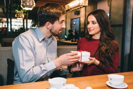 Picture of man giving a present to a woman. They are looking to each other and smiling a bit. They are sittin in restaurant.