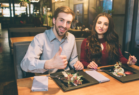 Advertising picture of man and woman sitting at the table with some food on it. They are looking to the camera and smiling. Man is showing his big thumb up. Stok Fotoğraf