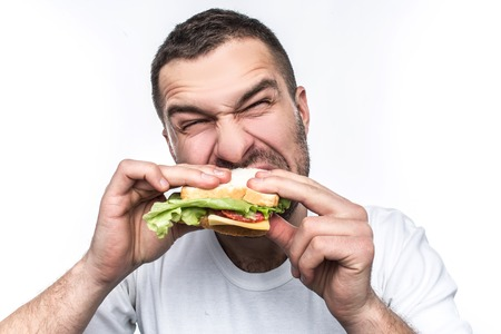 Funny and hungry guy is eating some fast food. He is hungry like a wolf. Man is biting sandwich very hard. Isolated on white background.