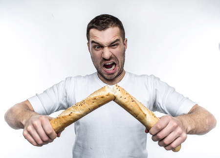 Emotional picture of strong guy breaking a baguette in the middle of it. The bread is fresh but nit very healthy. This freak guy likes to do this kind of stuff. Isolated on white background. Stock Photo