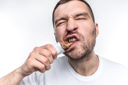 Una imagen cercana de chico comiendo dulce barra de chocolate con nouga. Él está mordiendo un gran pedazo de estos dulces. El joven es fanático de todo lo dulce. Aislado sobre fondo blanco