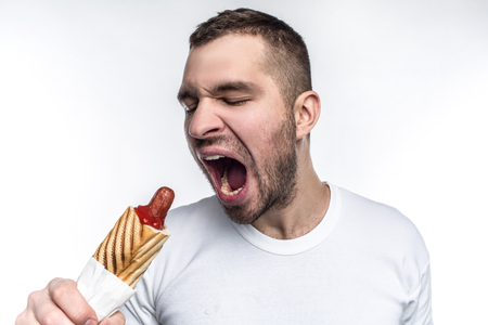 A picture of man that likes oily fast food. On this picture he wants to bite a big piece from fat hot dog. Man looks weird but brutal. Isolated on white background.