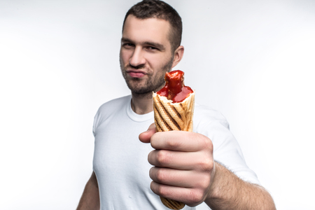 This man is holding big, fat but tasty hot dog. He looks brutal and serious. He recommend to eat this food because it is delicious. Isolated on white backgrond.