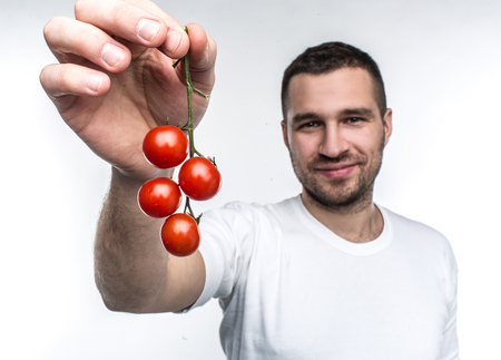 Attractive and handsome man is holding a ramus of cherie tomatoes. This vegane likes to eat every fruit and vegetable in a world. He recommends to eat only good food. Isolated on white background.