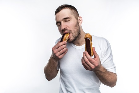 Strong and well-built guy is standing and eating eclair. Also he has another eclair in the other hand. Young man likes to eat oily fast food and sweet food as well. Isolated on white background.
