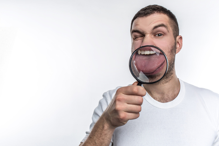 Man with magnifying glass is looking straight ahead and showing his tongue through the glass. Isolated on white background. Stok Fotoğraf