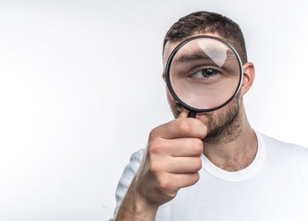 Man with loupe is looking straight ahead and showing his eye through the glass. He is an investigator. Isoolated on white background. Stock Photo