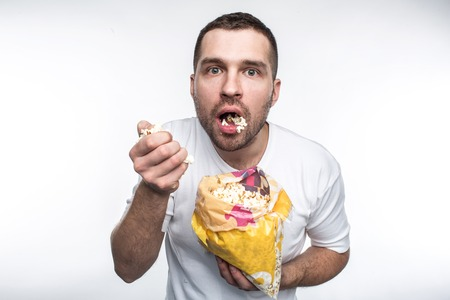 Amazed guy is holding a small pack of good popcorn and eting it. He has opened his mouth. He is not eating popcorn very accurate. Isolated on white background.