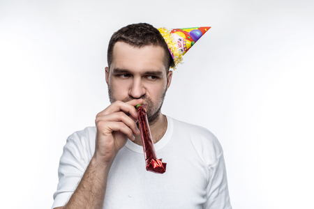 Unhappy guy is on party. He doesnt know how to stay happy and glas during celebration. Isolated on white background. 版權商用圖片