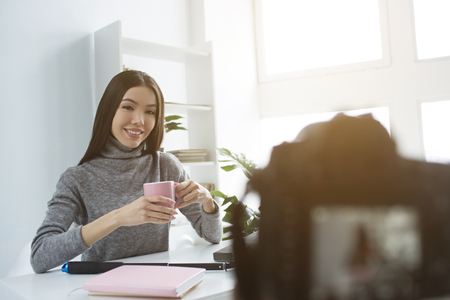 Nice and attractive girl is sittingat the table and drinking tea from pink cup. She is doing that in front of camera that recording it. She is looking to it and smiling.