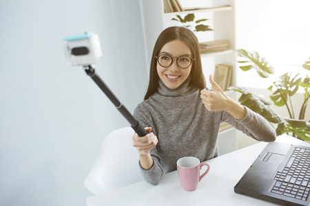 Beautiful blogger is sitting at the table in bright room and taking selfie using a selfie-stick for that. She is looking to camera and smiling.