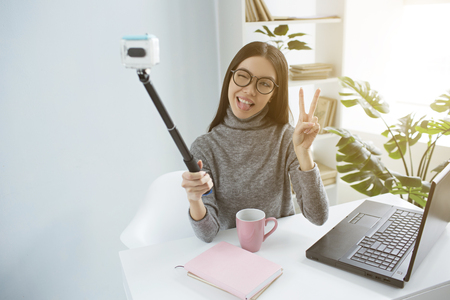 Cool brunette is sitting in a bright room and taking a selfie on camera using selfie-stick for that. She is showing a piece symbol on camera and closed one of her eyes. Girl looks nice and adorable.