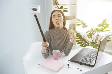 Funny young woman is showing her tongue to the camera. She is blogger and recording her video at home.