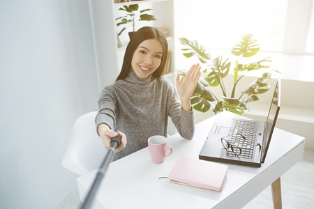 Nice girl sitting in a bright shiny room and recording video using selfie stick for that. She is waving to her followers, smiling and greeting them. Stock Photo