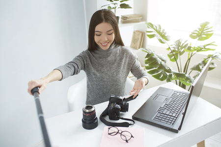 Dark-haired girl is sitting at the table and streaming a video. She is showing her equipment for photoshoots to her followers. She is excited and happy. Stok Fotoğraf - 98927615