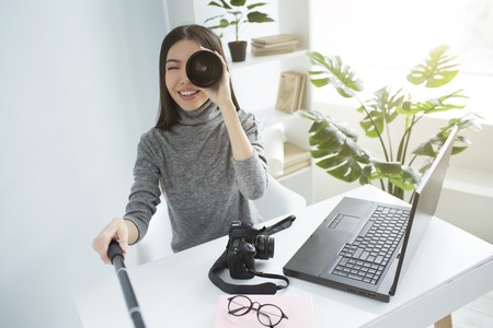Funny picture of a girl sitting at the table in a big bright room and recording video. She is looking to video camera through the photo cameras lens. Pretty girl is smiling.