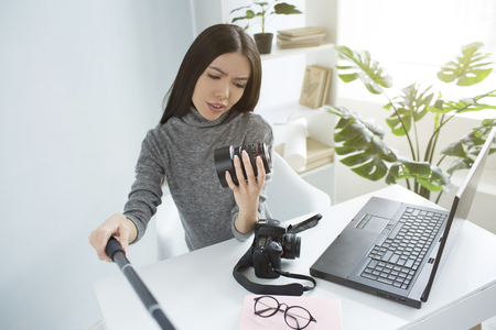 Professional blogger is sitting at the table and recording a video where she is looking to the cameras lens and studying it. She looks serious and cocncentrated.