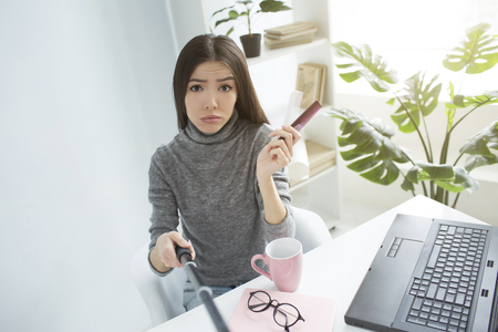 Sad and dissapointed blogger is sitting in a bright room and looking to the camera. She is upset. Girl holds two small hair brushes in her hands. She is recording it on camera that is on selfie-stick.