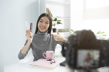 Beauty blogger is showing her hair brushes ckean and in good condition. She is looking at them and showing big thumb up. Camera is recording everything. Stok Fotoğraf