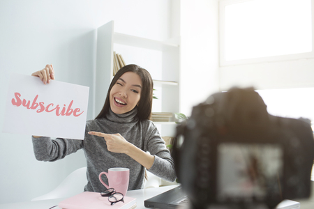 A picture of girl recording video on her camera. She holds a piece of paper with printed words on that. She alsp points on the paper which means she recommends everybody to subscribe to her channel.