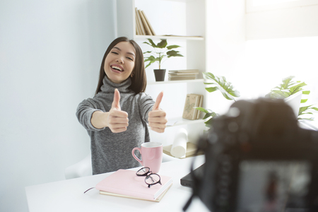 A picture of happy and delightul girl sitting at the table and recording her new vlog. She is showing her big thumbs up on her both hands and smiling. Young woman looks very good and nice.