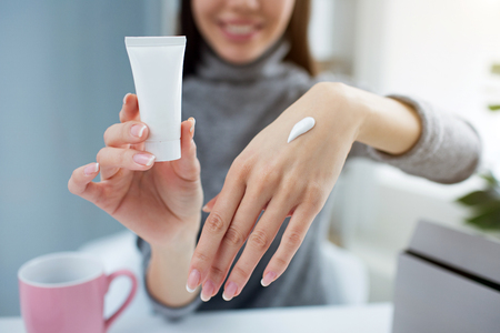Close up of girls hands. She is holding a small tube with hand cream in one hand and showing her other hand with some cream on it. Young blogger is smiling. Cut view. Stock Photo