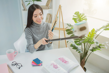 Blogger taking selfie with brushes. She is looking down to them and smiling. Girl is sitting at the table in a bright and large room. Zdjęcie Seryjne