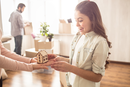 Beautiful and cheerful small girl is holding a wood house in her hands. She is sharing it with her mother. The father is holding a box with stuff that needs to be unpacked. Stock Photo