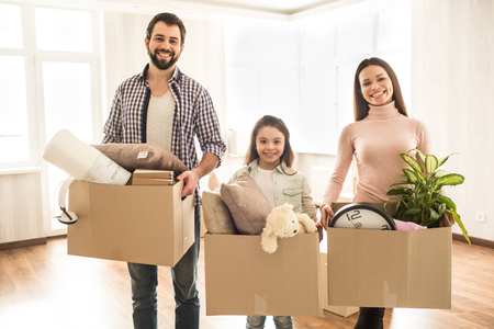 A picture of family where everybody is holding a box of different stuff in their hands. They are standing in an empty room. These people look happy and smiling, looking straight froward on camera.