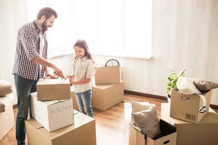 Father and daughter are unpacking boxes together. They have a lot of work to do. They are without their mother right now. This people look happy and satisfied.