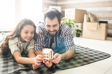 Father and his daughter are lying on blanket on the floor. They are holding a samm house that is made out of wood. They are looking to it and smiling. Banco de Imagens