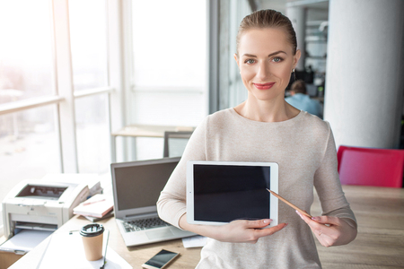 A picture of happy and cheerful woman having laptop in her hands. She has a pen in her left hand and show with it to the tablets screen.