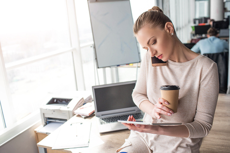 Beautiful girl is sitting at the adge of the table and looking at the tablet. Also she is talking on the phone and holding a cup of coffee. This business woman is very busy. Banco de Imagens